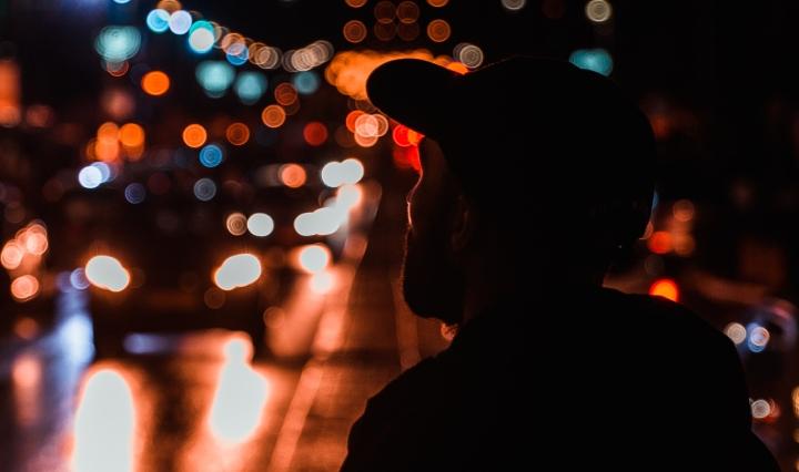 Hombre de espaldas observando el tráfico nocturno de la ciudad