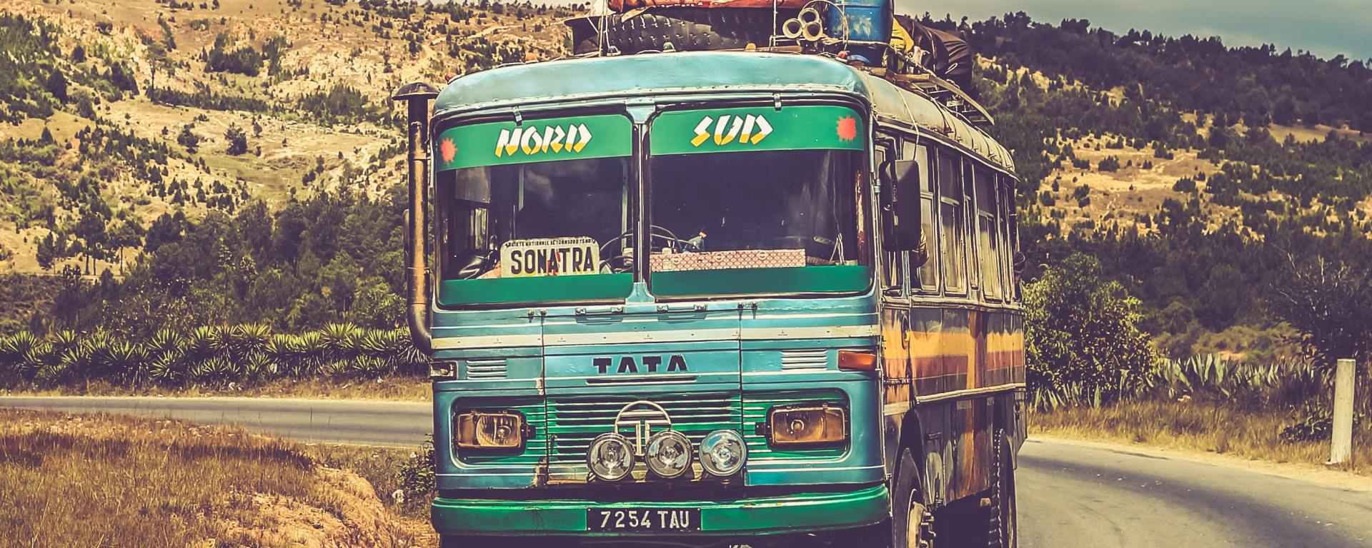 Autobús viejo, por la carretera de un paisaje agreste