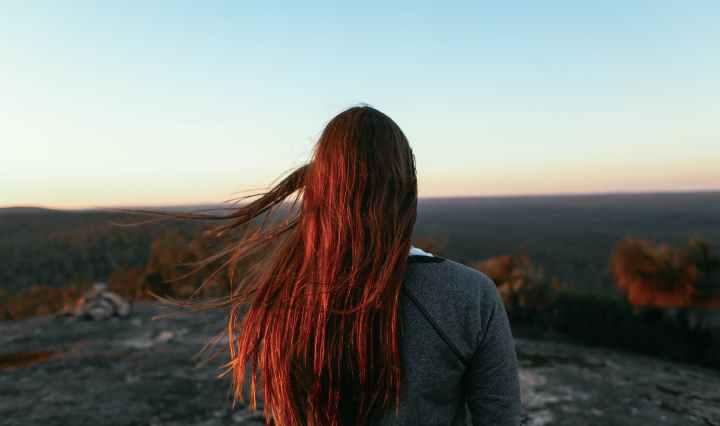Pelirroja de espaldas contemplando el horizonte en medio del monte.