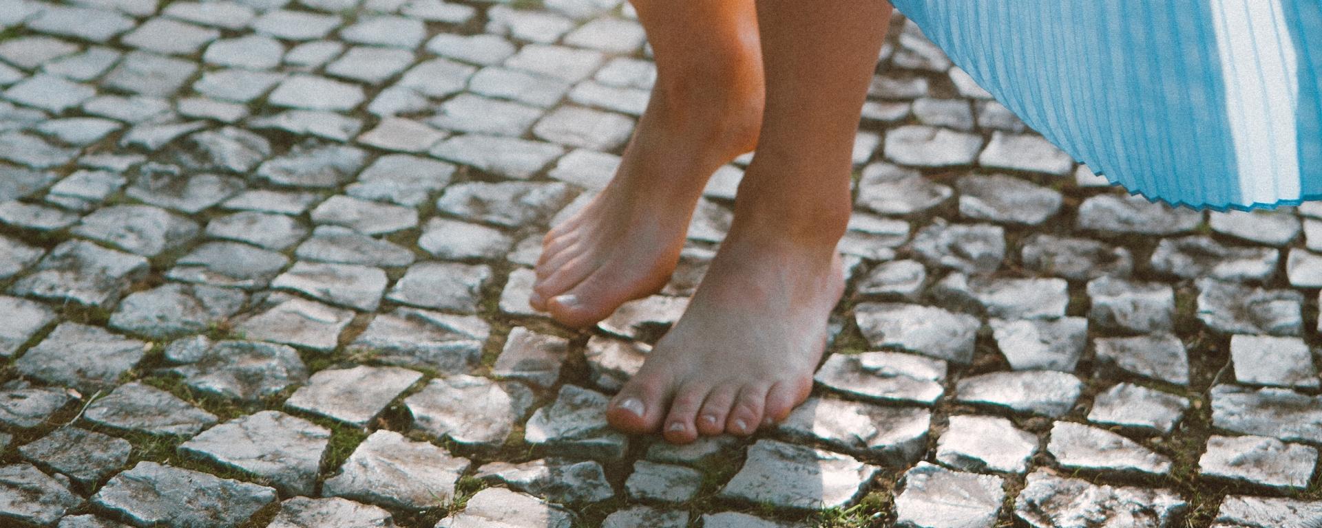 Mujer de vestido azul caminando descalza por el pavimento empedrado.